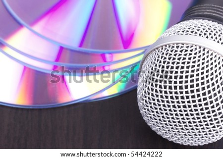 Vocal microphone and audio discs, closed-up on black table - stock photo