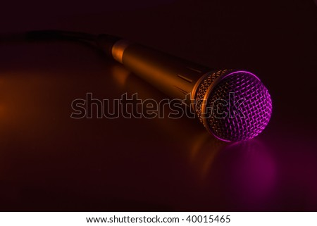 Vocal mike with cord in a color light - stock photo