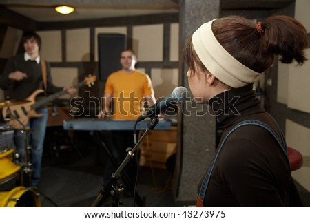vocalist girl near microphone. focus on head of microphone. electrical guitar player and keyboarder in out of focus - stock photo