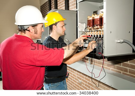 Vocational education student learns how to repair an industrial power distribution center. - stock photo