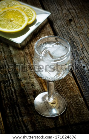 vodka and lemon slices on a wood background