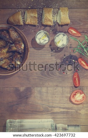 Vodka, gin, tequila. fried chicken legs and fried chicken wings , Cherry tomatoes, Spices, baguette, Italian food. Vodka, gin, tequila in a glass with ice on a wooden table, a reflection.  - stock photo