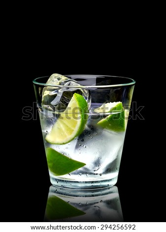 Vodka lime or gin tonic with ice in rocks glass on black background including clipping path - stock photo