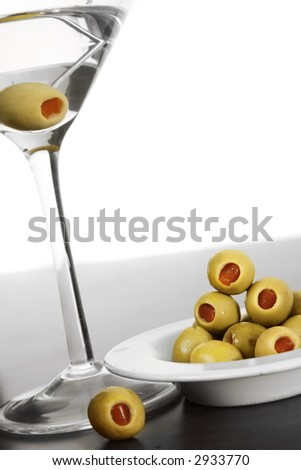 Vodka martini with olives and desaturated surroundings - stock photo