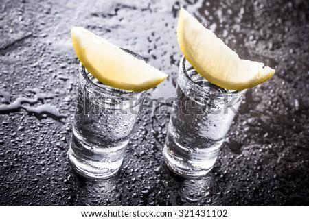 Vodka shot glass on black wet surface. - stock photo
