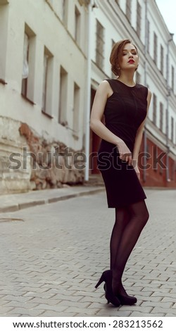 Vogue model in the black dress outdoor near building