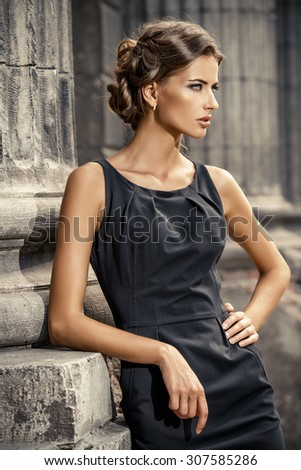 Vogue model wearing black dress posing over urban background. Fashion shot. - stock photo