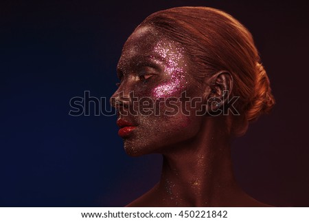 Vogue style portrait of a woman. Black makeup with glitter. Dark background. Toned