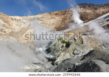 Volcanic landscape of Kamchatka: brimstone and fumarole field in crater of active Mutnovsky Volcano. Russia, Far East, Kamchatka Peninsula. - stock photo