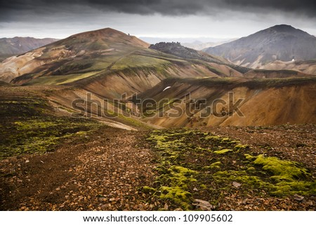 Volcanic landscape with moss and dramatic cloudy sky in Iceland - stock photo