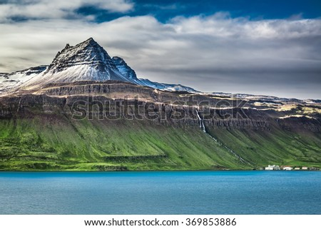 Volcanic mountain over fjord in Iceland - stock photo