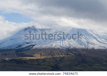 volcano mount Saint Helens decapitated top with glacier and surrounding bogland with trenches and  in clouds - stock photo