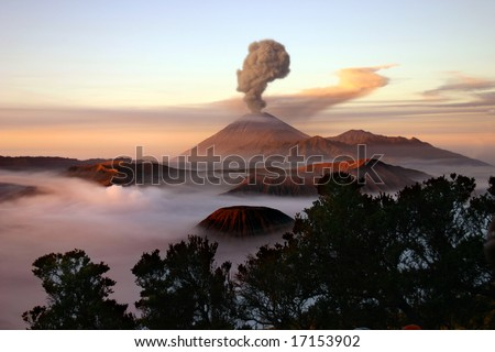 Volcano with a plume of smoke at sunrise.