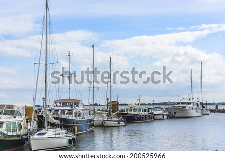VOLENDAM, NETHERLANDS - JUNE 18, 2014: Passenger liners, boats and sail boats in Volendam Harbour. Volendam - a small town that has preserved the tradition of Dutch fishing villages.