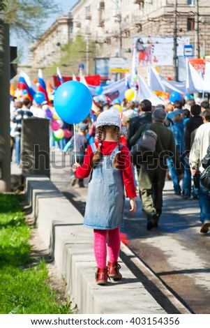 VOLGOGRAD, RUSSIA - MAY 1, 2011: Girl with balloon takes part in the May day demonstration in Volgograd - stock photo