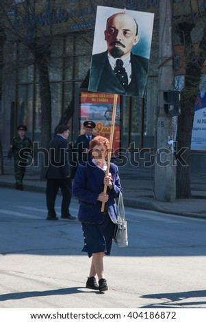 VOLGOGRAD, RUSSIA - MAY 1, 2011:Woman with portrait of the Soviet founder Vladimir Lenin takes part in the May day demonstration in Volgograd - stock photo
