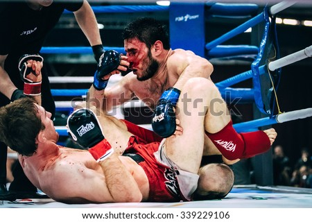Volgograd, Russia - October 24, 2015: two athletes MMA ground fighting, one of athletes bloody wound during Championship of Russia on mixed martial arts - stock photo