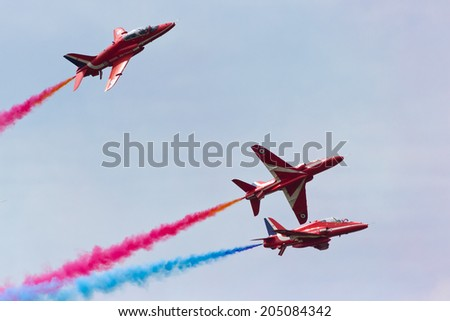 VOLKEL, NETHERLANDS - JUNE 14: RAF Red Arrows performing at the Royal Netherlands Air Force Days June 14, 2013 in Volkel, Netherlands.  - stock photo