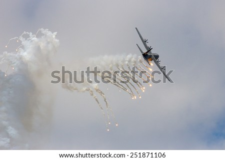 VOLKEL, THE NETHERLANDS - JUNE 15: Danish Air Force C-130 Hercules firing off flares during the Dutch Air Force Open Day on June 15, 2013 in Volkel, The Netherlands  - stock photo