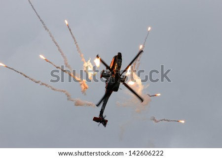 VOLKEL, THE NETHERLANDS - JUNE 15: Dutch Army AH-64D Apache making a looping while firing flares on the Dutch Air Force Open Days. June 15, 2013 in Volkel, The Netherlands