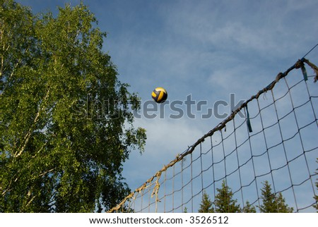 volleyball ball above the shabby net and cloudscape - stock photo
