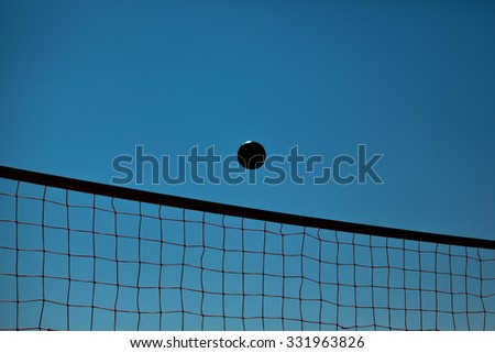 Volleyball Ball Over Net On Background Of Blue Summer Sunny Sky. Ball Flying Through Air On Beach