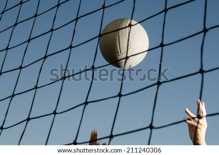 Volleyball flying through air with hands visible - stock photo
