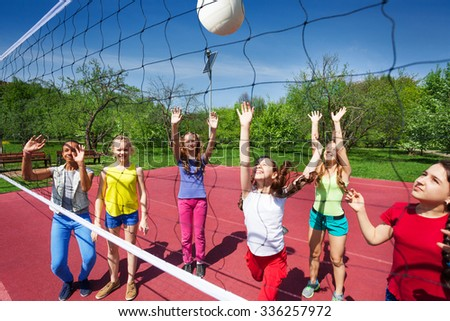 Volleyball game with playing teenage children on the playground during summer sunny day - stock photo