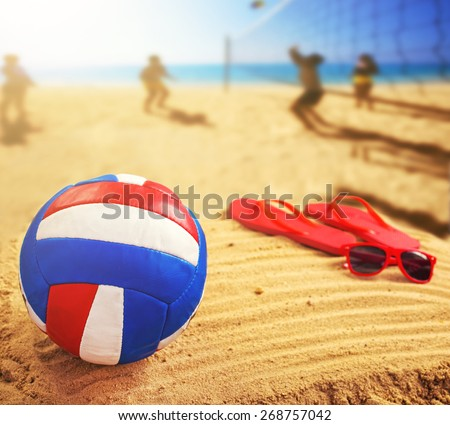 Volleyball in the sand with sandals at the beach - stock photo