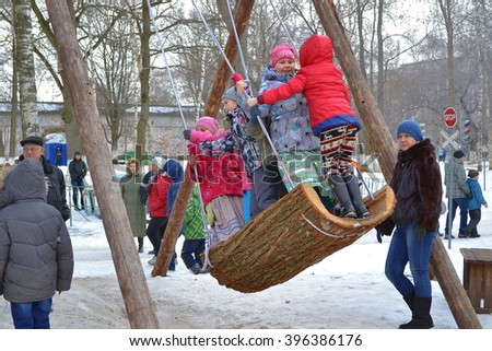 Vologda, Russia - March 13, 2016: Children swinging on a swing made from the bark of a tree on a holiday Maslenitsa in the city of Vologda. Russia March 13, 2016.