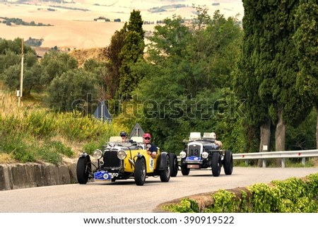 VOLTERRA (PI), ITALY - SEPTEMBER 19: A yellow Aston Martin and a black Wolseley Hornet Special take part in the GP Nuvolari classic race on September 19, 2015 near Volterra. Both were built in 1933. - stock photo
