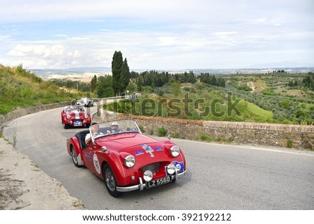 VOLTERRA  (PI), ITALY - SEPTEMBER 19: Two red Triumph TR2 sport, followed by an A-H, take part in the GP Nuvolari on September 19, 2015 near Volterra (PI). The Triumphs were built in 1954 and 1955. - stock photo