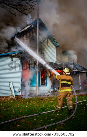 volunteer firefighter spraying water on house  - stock photo