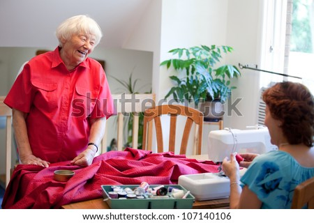 Volunteer helping senior with sewing project - stock photo