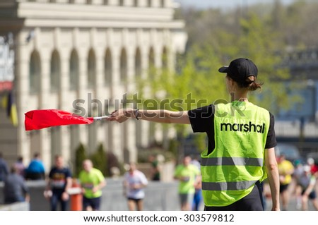 Volunteer Marshal shows the direction of movement of sportsmen runners