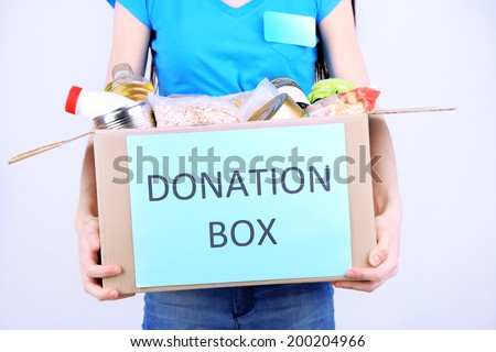 Volunteer with donation box with foodstuffs on grey background - stock photo