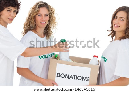 Volunteer women putting food in donation box on white background - stock photo