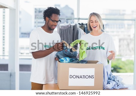 Volunteers looking at a donation box full of clothes - stock photo