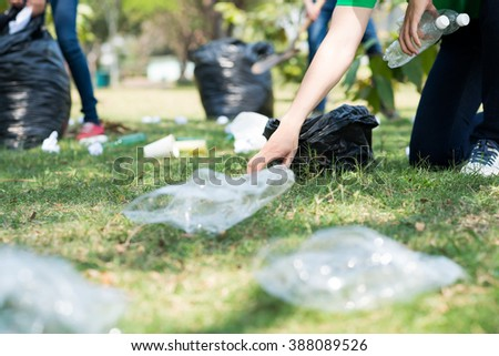 Volunteers picking up trash on a meadow - stock photo