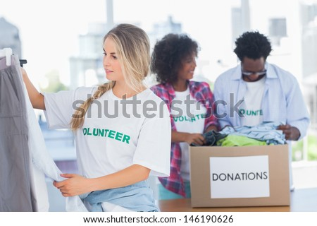 Volunteers putting clothes in clothes rail in their office - stock photo