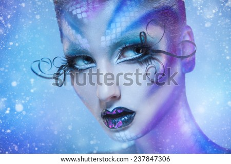 Voluptuous young adult girl looking away with creative body art and snow on background in studio - stock photo