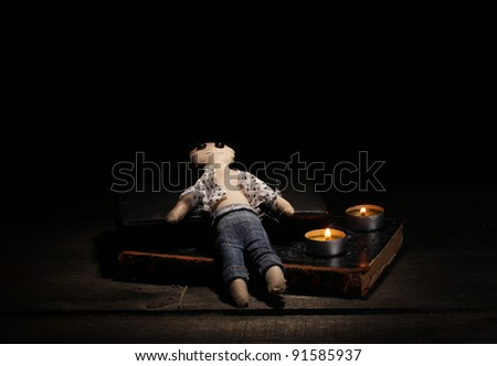 Voodoo doll boy on a wooden table in the candlelight - stock photo