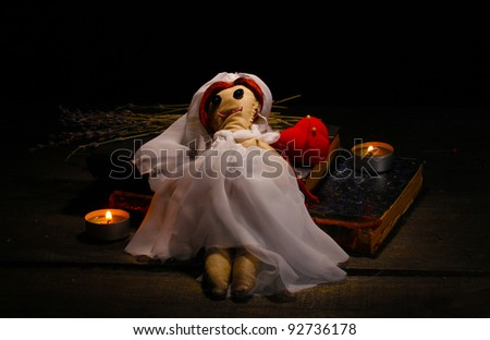 Voodoo doll girl-bride on a wooden table in the candlelight