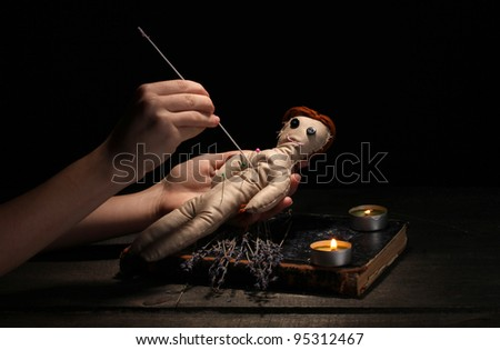 Voodoo doll girl pierced by a needle on a wooden table in the candlelight - stock photo