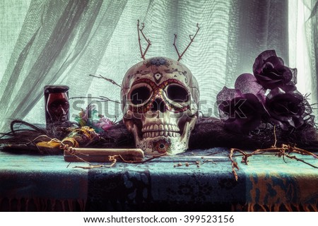 Voodoo Evil Skull Ritual. Voodoo related objects on a table including a skull, a knife and candles. - stock photo
