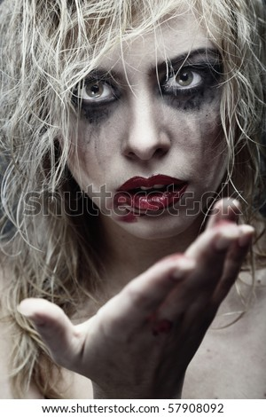 Voodoo female witch with dirty makeup and blood on the hand. Artistic colors and darkness added - stock photo