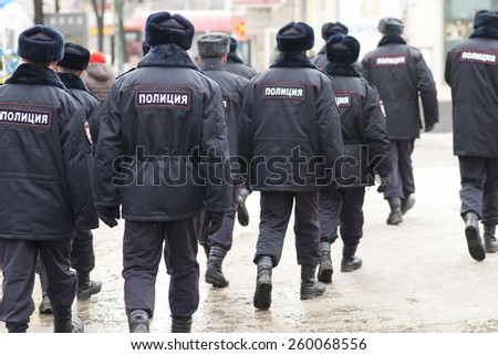 "VORONEZH, RUSSIA - MARCH 1: Group of unidentified Russian policemen walk to the rally dedicated to Boris Nemtsov murder on March 1, 2015, Voronezh, Russia. Caption on their backs mean ""Police"". - stock photo"