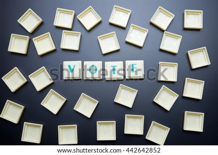 Vote concept. The words spelled by letters on blackboard background. - stock photo