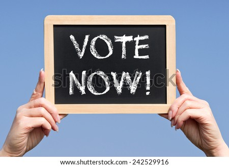 Vote Now ! - Female hand with chalkboard and text - stock photo