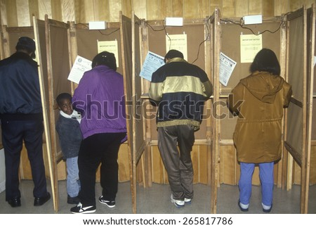 Voters and voting booths in a polling place, CA - stock photo
